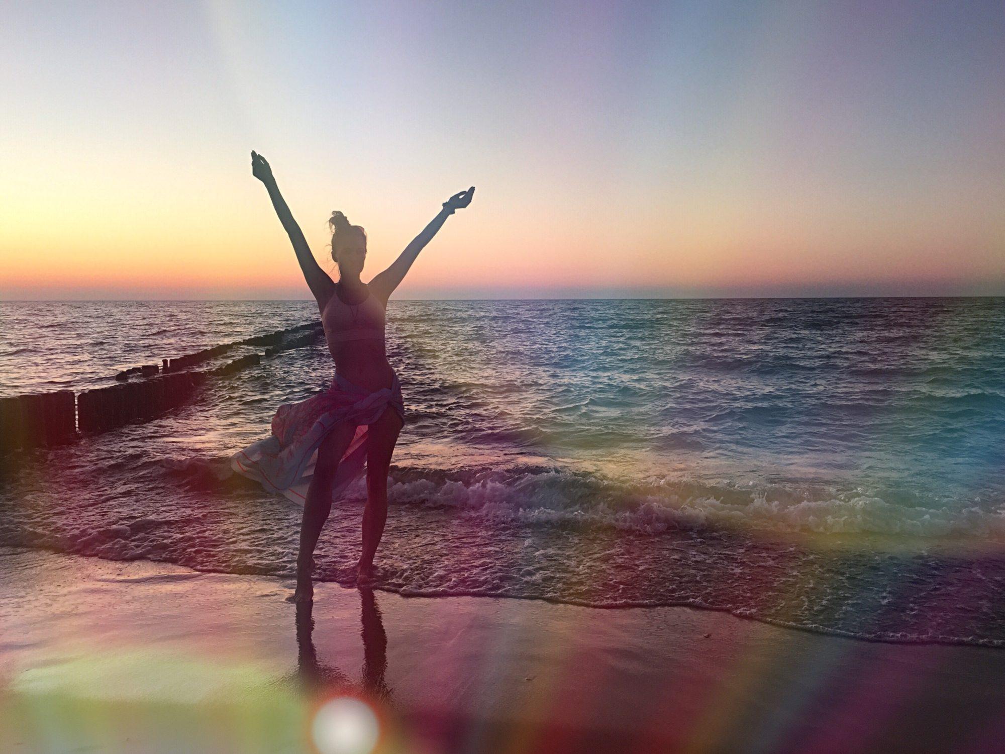 Piękny zachód słońca nad morzem Bałtyckim i człowiek otwierający ramiona w zachwycie