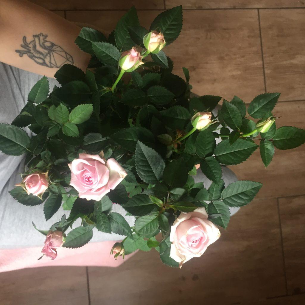 bukiet kwiatów róży w dłoniach i tatuaż serce na przedramieniu