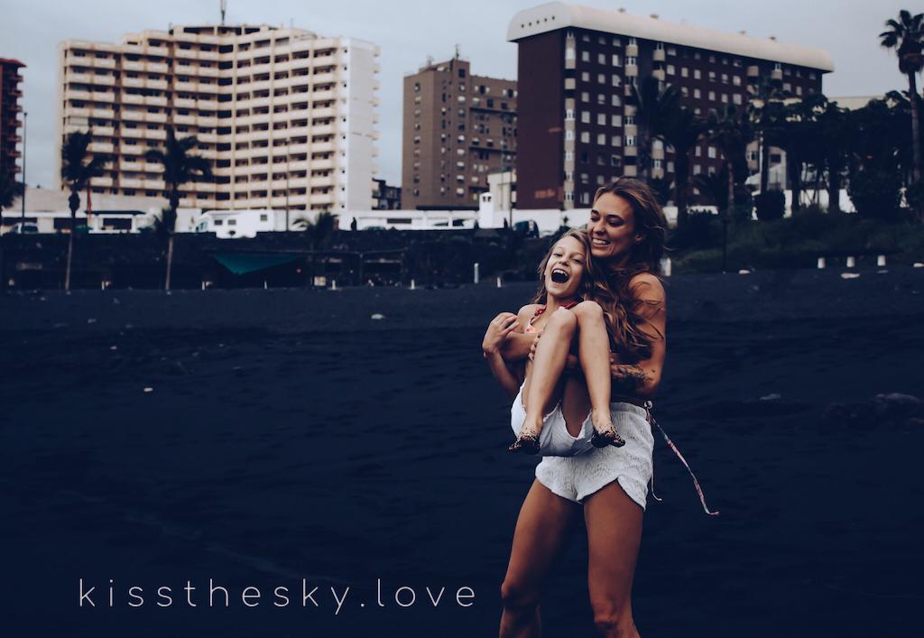 Mama i córka bawią się na czarnej plaży