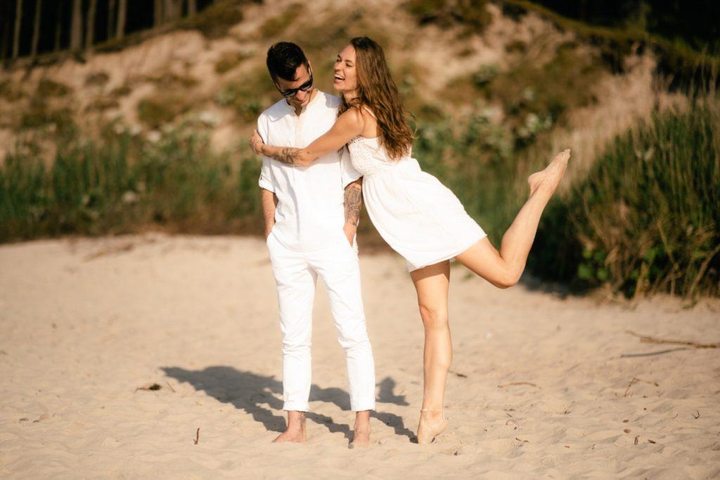 Uśmiechnięta para ubrana na biało na plaży